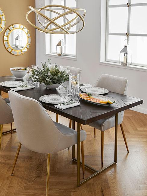 jadania w stylu glamour z okazałą złotą lampą wiszącą i aksmaitnymi beżowymi krzesłami