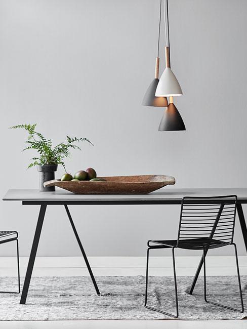 Minimalistyczny czarny stół do jadalni z trzema lampami wiszącymi o różnej długości