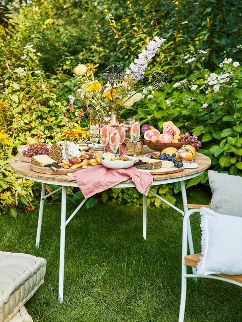 Okrągły stół w ogrodzie zastawioany jedzeniem i udekorowany na letnie przyjęcie