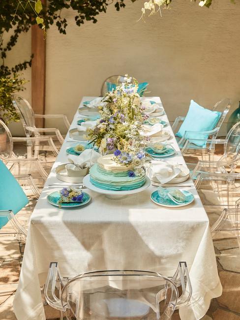 Długi, prostokątny stół z obrusami, trukusowymi talerzami oraz kwiatowymi dekoracjami na letnie przyjęcie
