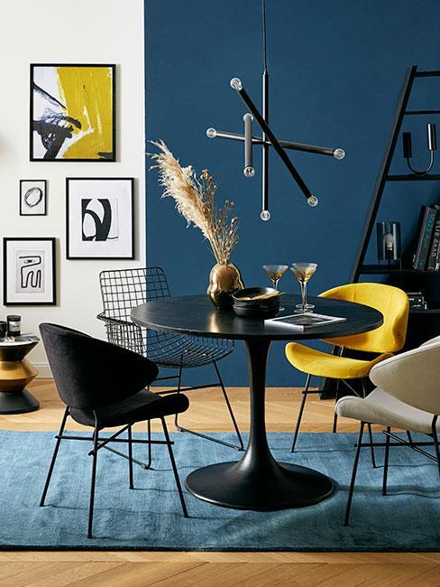 Nowoczesną jadalnia z czarnym okrągłym stołem i nowoczesną wieloramienną czarną lampą otoczona żółtym, czarnym i beżowym krzesłem z aksamitu na tle niebieskiej ściany