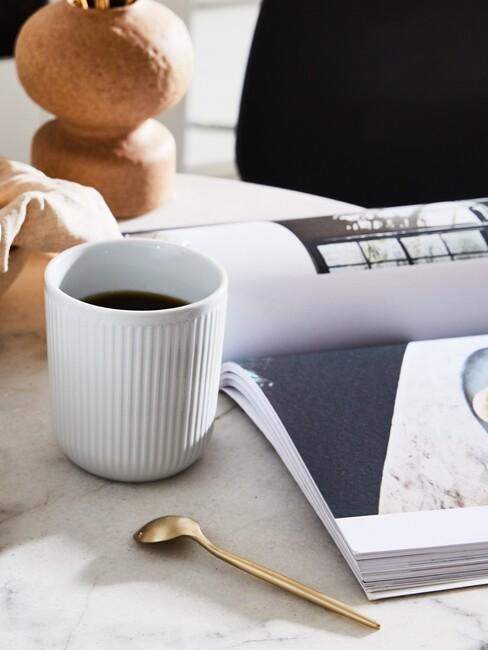 Biała, ceramiczna filiżanka z espresso obok magazynu wnętrzarskiego