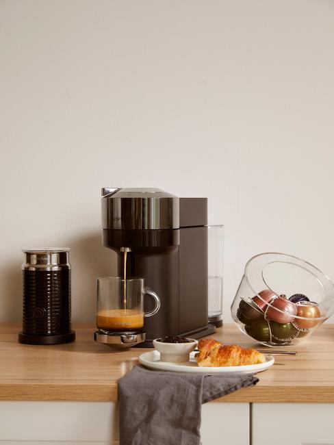 Ekspres do kawy kapsułkowy na drewnianym blacie, obok pojemnika z kapsułkami, termosem na kawę i białtym talerzem