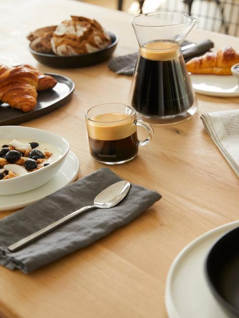 Szklana filiżanka z espresso obok dzbanka z kawą na stole ze śniadaniem