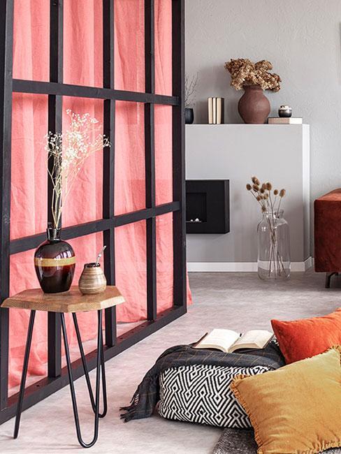 ścianka w stylu japońskim z różową zasłoną w salonie z białym minimalistycznym kominkiem, poduszkami podłogowymi i stolikiem z drewna