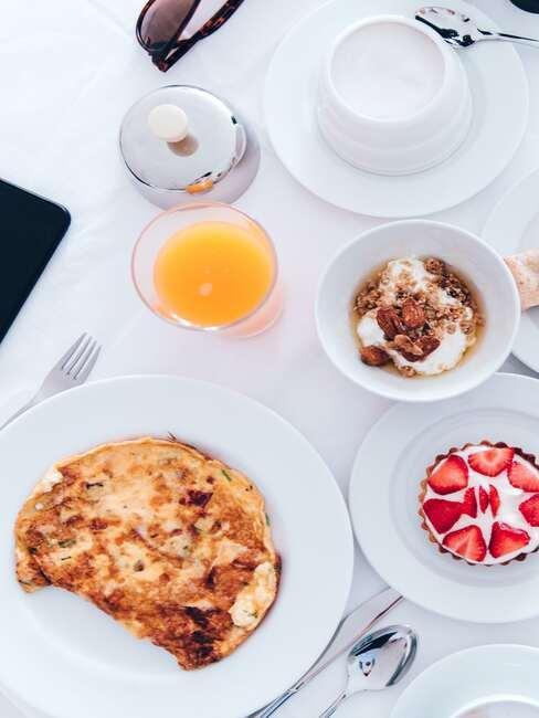 Omlet na białym talerzu obok szklanki z sokiem, muski z muesli i ciastkiem
