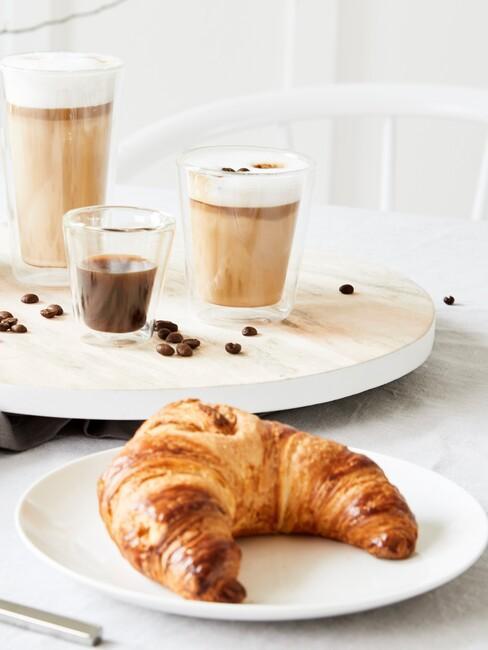 Zbliżenie na rogalika na białym talerzu obok deski z trzema rodzjami kawy