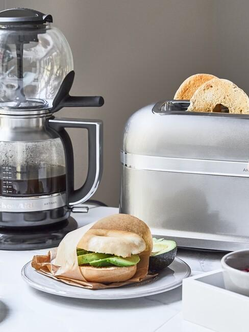 Bajgiel z awokabo obok srebrnego tostera i ekspresu przelewowego na kawę