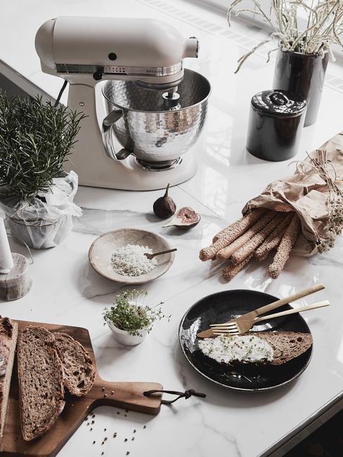 Kanapa z twarożkiem i kiełkami na czarnym talezu na blacie kuchennym obok robota kuchennego