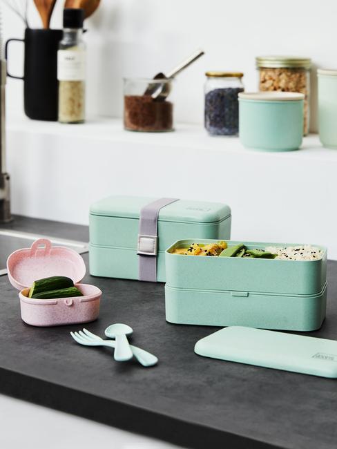 Turkusowe pudełka lunchowe na czarnym blacie w kuchni