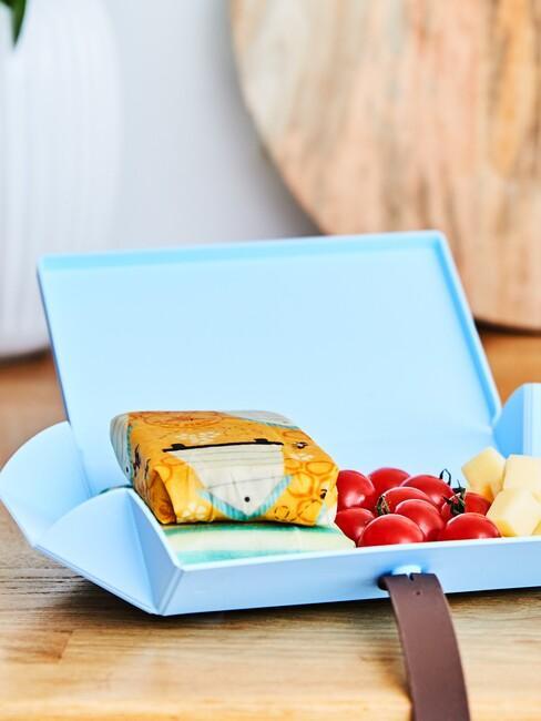 niebieskie pudełko lunchowe z kanpapką owiniętą w woskowijkę na drewnianym blacie