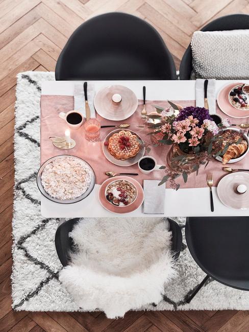 Biały stół zastawiony na śniadanie z białą zastawą talerzy, różowym obrusem oraz wazonem kwiatów
