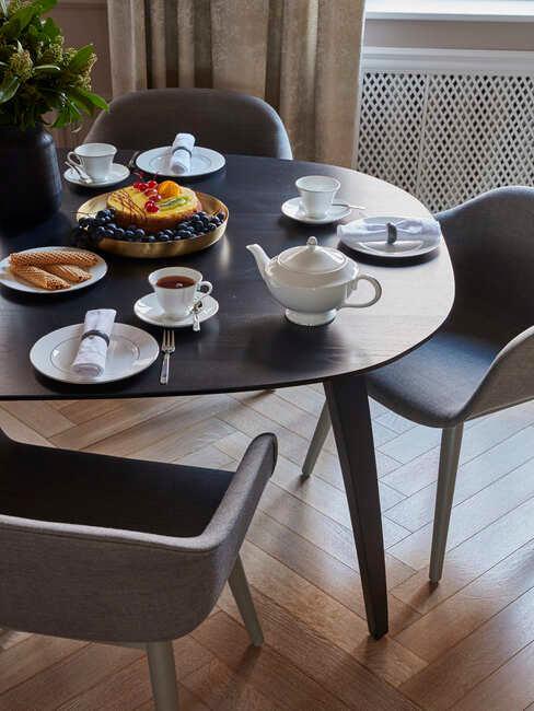 owalny, czarny stół z białym kompetem naczyń śniadaniowych