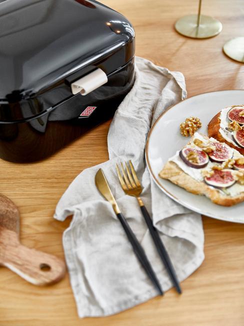zbliżenie na czarny chlebak, biały talerz z kanapkami i złote sztućce na drewnianym blacie