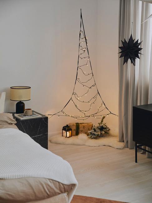 Biała sypialnia z fragmentem łóżka, czarnej szafki nocnej oraz choinki z lampek w rogu