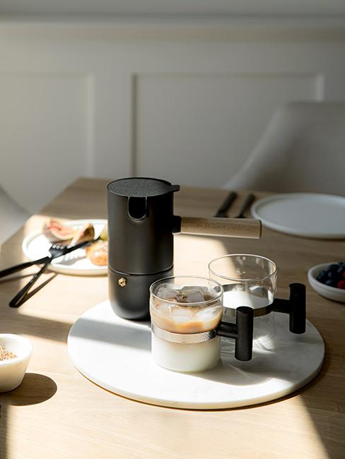 czarna designerska kawiarka z szklanymi kubkami do kawy na jasnym drewnanym stole