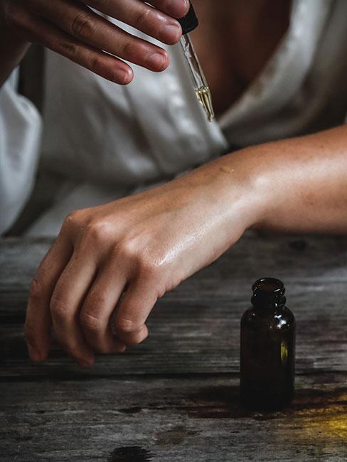 Zbliżenie na dłonie kobiety, która nakłada olejki eteryczne na dłoń