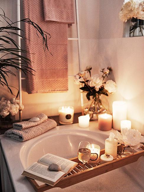 Zbliżenie na wannę z świeczkami, książką i ręcznikami