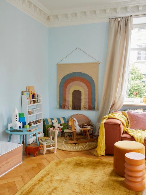 Kącik do zabawy dla dzieci w salonie w stylu skandnawskim z małym stoliczkiem, półkami oraz dywanem