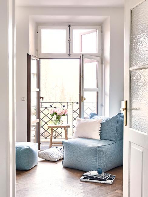 Zbliżenie na kącik wypoczynkowy z niebieskim fotelem z białą poduszką, niebieskim pufem przy wyjściu na balkon