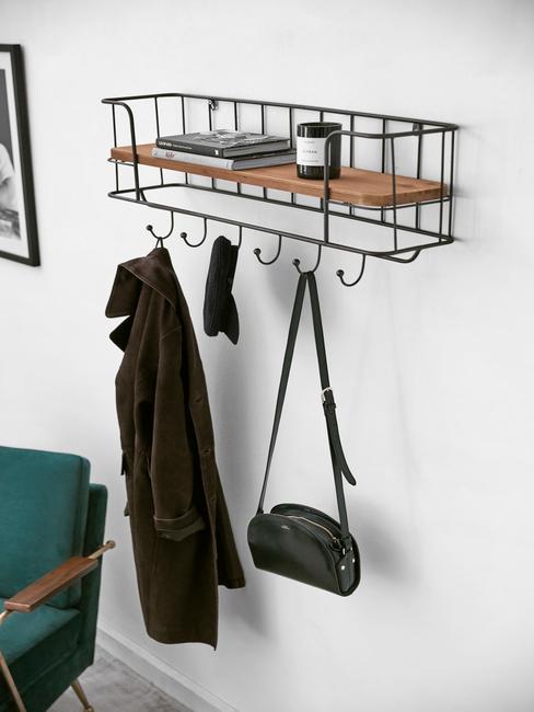 Zbliżenie na wieszak z półką w przedpokoju w stylu skandynawskim obok ciemnozielonego fotela