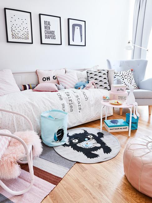 Pokój dziecięcy w stlu skandynawskim z sofą z poduszkami i narzutą, dywanem, obrazkami na ścianie