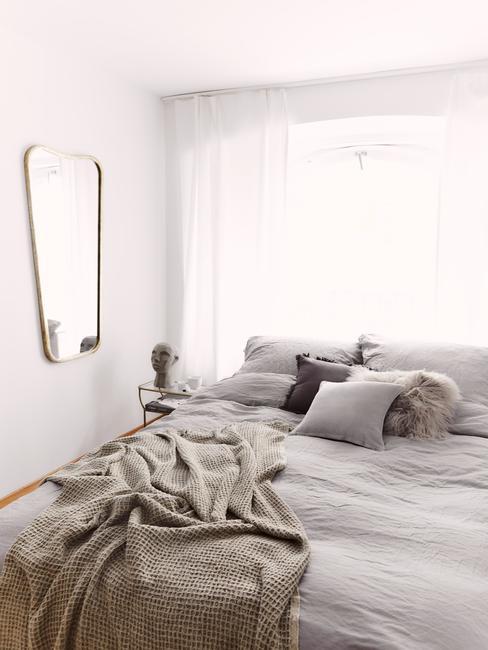 Zbliżenie na łożko w sypialni z szarą pościelom, beżowym kocem oraz lustrem w złotej ramie na ścianie