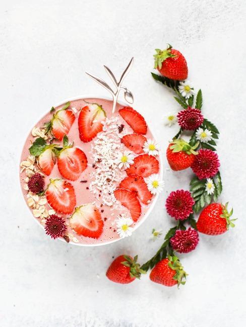 Biała miseczka na blacie ze smoothie bowl udekorowana truskawkami, wiórkami kokosowymi i płatkami owsianymi