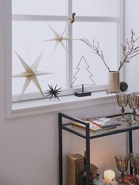 Zbliżenie na beżowe gwiazdy z paieru, choinkę z drutu i wazon z suszonymi gałązkami na parapecie