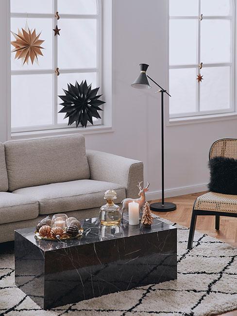 salon w stylu skandynawskim z beżową sofą, fotelem z rattanu, czarnym stolikiem kawowym z imitaci marmurz i gwiazdami z papieru przy oknie