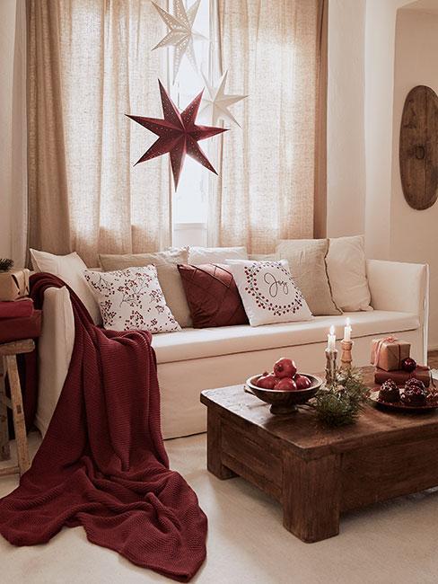 Salon z białą sofą, czerwonymi tekstyliami i białymi poduszkami świątecznymi z papierowymi gwiazdami na oknie w bieli i czerwieni przy stoliku kawowym z ciemnego drewna