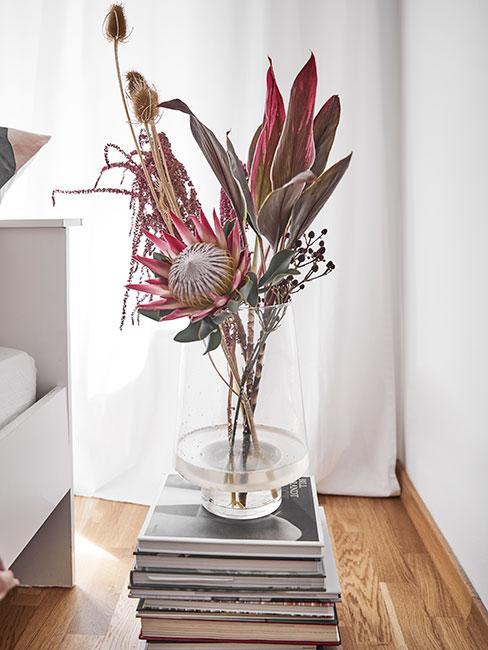 Stolik nocny z książek poustawianych w stos, na którym stoi wazon z suszonymi kwiatami