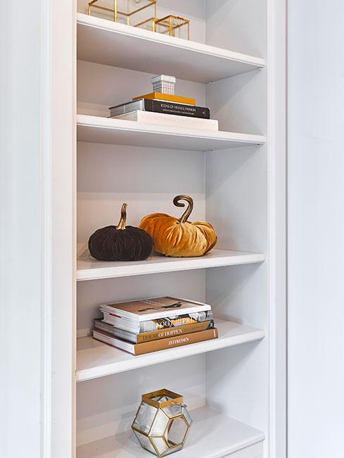Biały regał udeokorowany książkami, dyniami z aksamitu i świecznikami