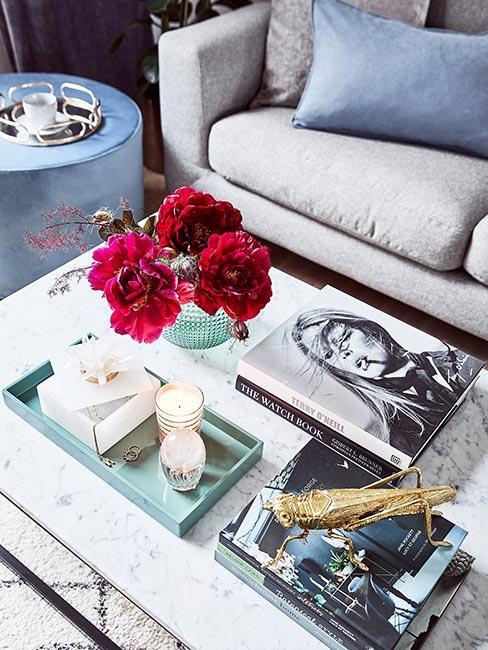 Książki leżące na stoliku kawowym obok eleganckich gadżetów