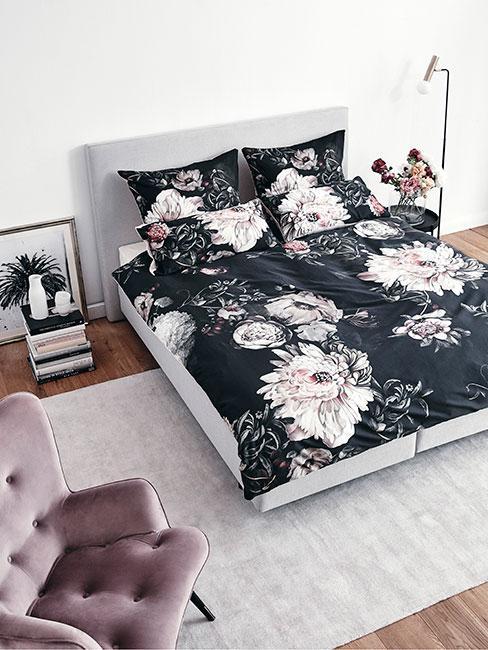 sypialnia z dużym szarym łóżkiem i czarną pościelą w duże kwiaty obok stolika z książek, na którym stoją białe wazony