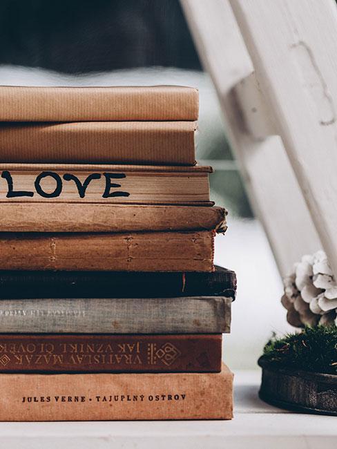 Książki ustawione w stos po białą drabiną