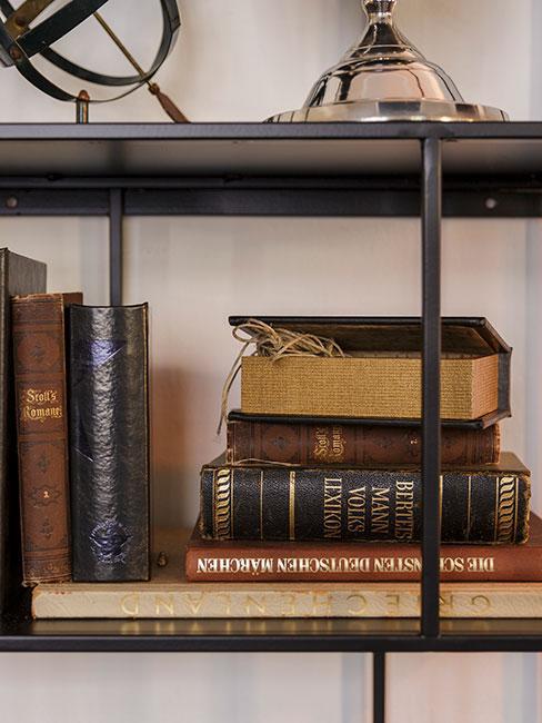 Czarny metalowy regał ze starymi książkami w skórzanych oprawach