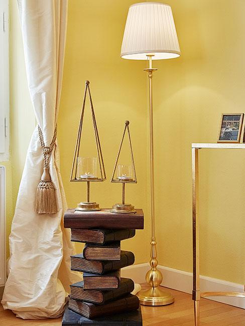 Stare książki w ciemnych skórzanych oprawach ustawione w stos, na których stoją dwa świeczniki w kształcie choinek