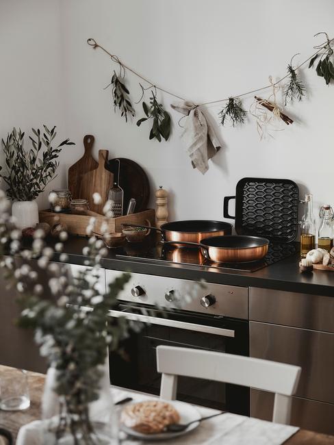 Biała kuchnia w stylu skandynawskim, ze srebrnym piekarnikiem, doniczką roślin oraz suszonymi ziołami