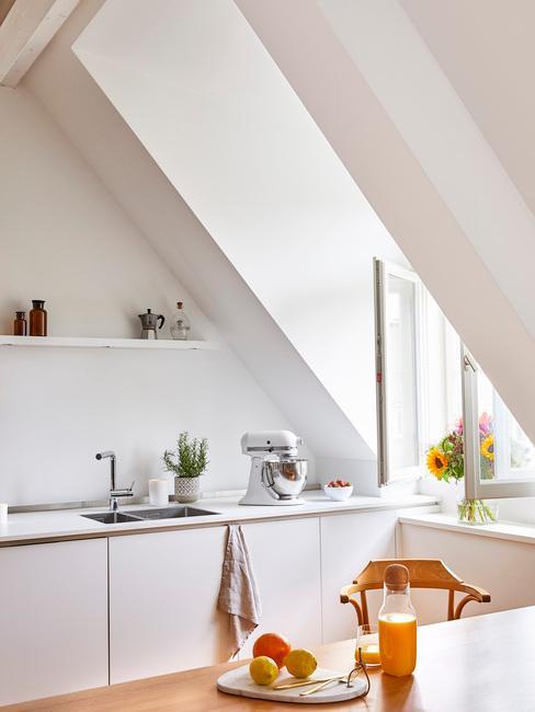 Kuchnia na poddaszu z białą ścianą, białymi frontami szafek oraz dekoracjami w postaci robota kuchennego oraz roślin