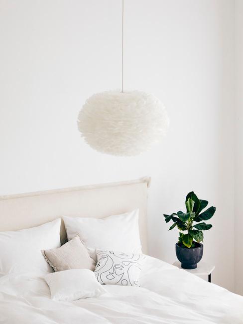 Biała sypialia z białym łóżkiem, pościelą, poduszkami, lampą oraz rośliną na stoliczku nocnym