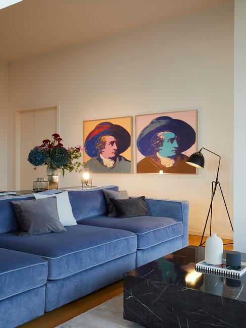 Wnętrze salonu z granatową kanapą, czarnym stoliczkiem kawowym oraz obrazami na ścianie