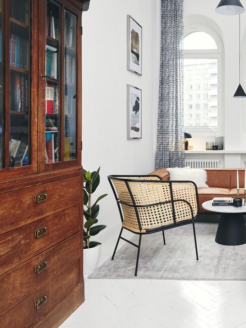 Salon ze skórzaną sofą, czarnym stolikiem, krzesłem z plecionki wiedeńskiej praz retro, drewnianą komodą