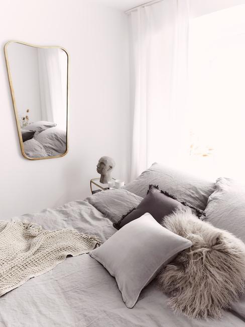 Fragment małej sypialni w blok, z łóżkiem z dużą ilością poduszek, lustrem oraz stoliczkiem nocnym