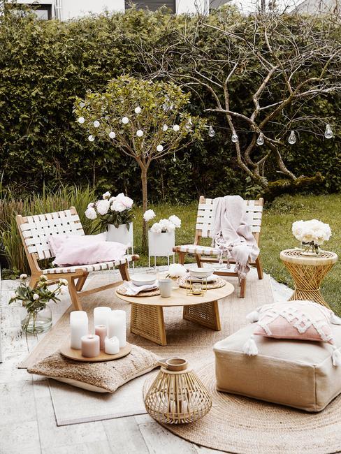 Taras w ogrodzie z jutowym, zewnętrznym dywanem, krzesłami, okrągłym stoliczkiem oraz pufami