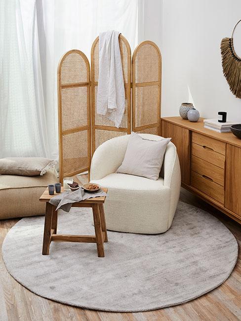 Beżowy fotel tapicerowany przed parawanem z rattanu obok komody z drewna na okrągłym dywanie
