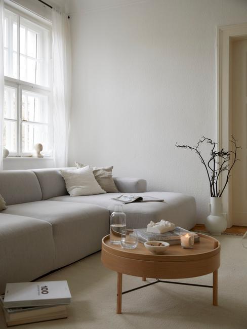 Beżowy salon w stylko skandynawski z jasnoszarą, narożną sofą oraz drewnianym stoliczkiem kawowym i wazonem z gałęziami