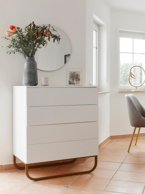 Zbliżenie na białą komodę w stylu skandynawskim w salonie z wazonem z kwiatami oraz lustrem nad nią