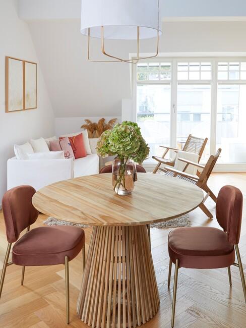 Zbliżenie na okrągły, drewniany stół oraz dwa tapicerowane fotele w salonie z białą sofą w tle