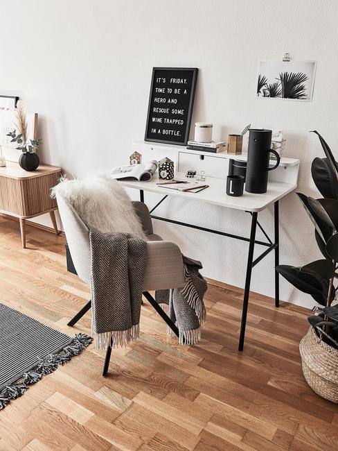 Białe biurko z metalowymi, czarnymi nóżkami, beżowym fotelem z kocem i poduszką oraz akcesoriami